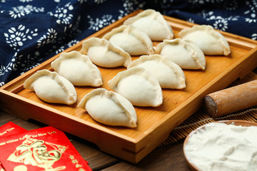 raw dumplings on wooden plate with flour and rolling pin and red packet,Chinese word translation:happiness