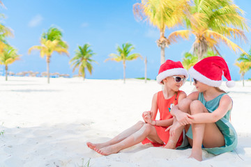 Adorable little girl have fun in Santa hat celebrating Christmas on the beach