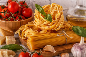 Products for cooking - pasta, tomatoes, garlic, olive oil, basil.