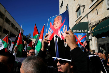 Palestinian protestors hold Palestinian flags and pictures of U.S. President Donald Trump during a demonstration in a street in east Jerusalem