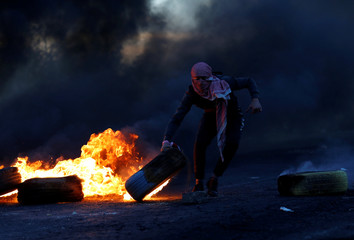 Palestinian moves a tire during clashes with Israeli troops at a protest near the Jewish settlement of Beit El near Ramallah