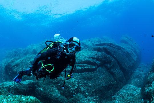 woman scuba diving over rocks in the Mediterranean Sea