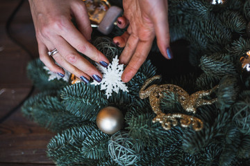Decorator prepares christmas wreath with fir branches and toys