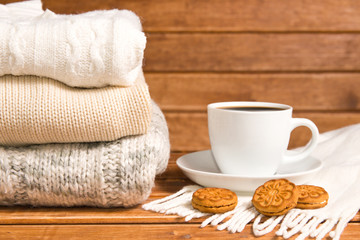 Stack of cozy knitted warm sweater , wooden background . Sweaters in retro Style and a Cup of hot chocolate. The concept of warmth and comfort.