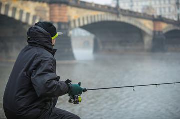 Spoed Fotobehang Vissen Alone fisherman, trying to catch fish in early morning