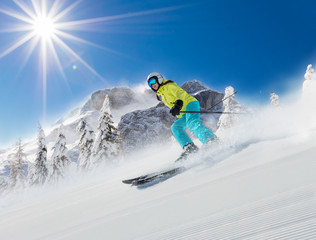 Young woman skier running down the slope in Alpine mountains.
