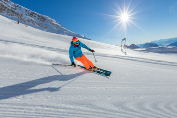 Skier on piste running downhill in Alpine landscape.