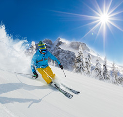 Fototapete - Skier on piste running downhill in Alpine landscape.