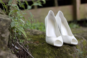 White Wedding Shoes on a Mossy Stone Wall