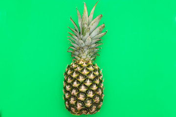 Tropical Pineapple fruit on a green background. Flat lay