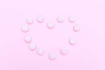 Pink candies are lined in the shape of a heart on a pink background. Flat lay