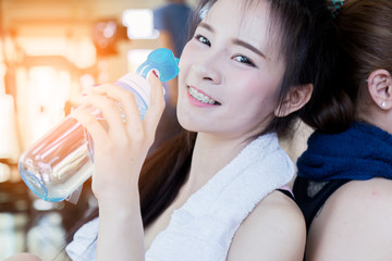 asian strong woman fit and firm healthy concept hand hold fresh water drink bottle at gym