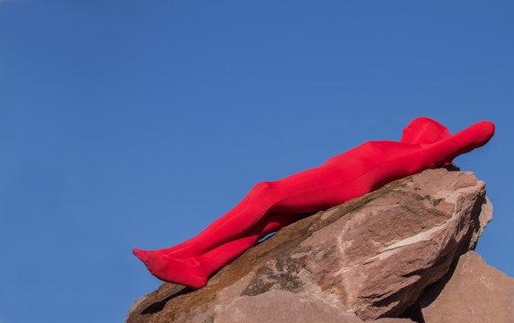 Mensch mit rotem Morphsuit auf Fels
