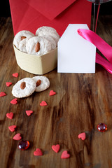 White cookies with almond in heart-shaped box. Tiny hearts are scattered around. Treats for Valentine's Day