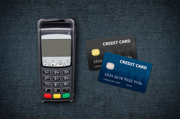 Payment terminal and credit cards on jeans background