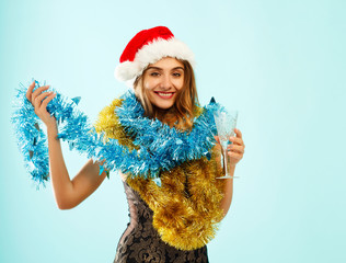 Young attractive Santa girl in red dress over blue background