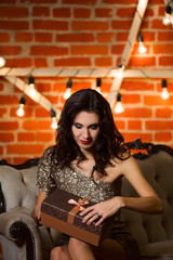 Portrait of young happy beautiful woman in golden dress holding present box