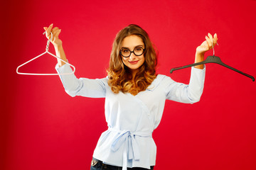Young happy woman holding two empty hangers over red background