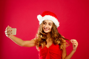 Young happy Santa woman in red dress taking her selfie over red background