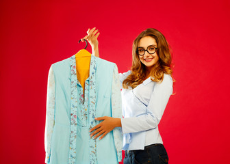 Young happy woman holding hanger with clothes over red background
