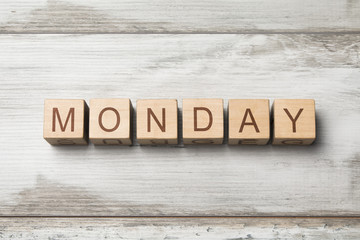 MONDAY word written on wooden cubes on wooden background