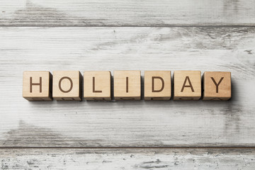 HOLIDAY word written on wooden cubes on wooden background
