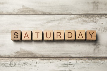 SATURDAY word written on wooden cubes on wooden background