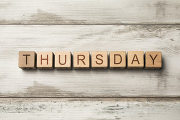 Thursday word written on wooden cubes on wooden background