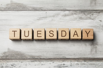 TUESDAY word written on wooden cubes on wooden background