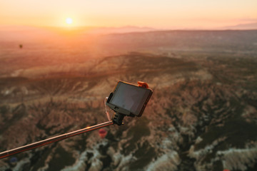 A man in a balloon takes a picture of the landscape of Cappadocia at dawn. Flight in a hot air balloon is one of the main attractions of Turkey.