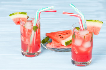 Watermelon lemonade with ice and mint leaves. Homemade lemonade of ripe berry with red and green ripes. Glass of cold watermelon tea. Refreshing summer drink. Cocktail on a wooden background