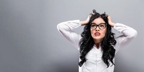 Young woman feeling stressed on a solid background