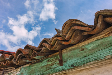 Vintage wooden roof with red tiles and eaves detail under blue s