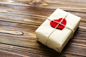 gift box wrapped in kraft paper and red wooden heart on wooden table
