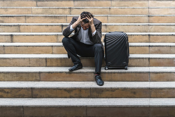 Unemployed businessman stress sitting on stair, concept of business trip failure and unemployment problem, work life balance.