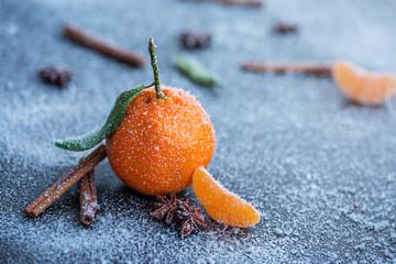 Frische Klementine mit  Zimtstange mit winterlichen Hintergrund