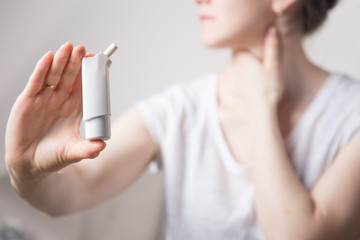 a woman uses a needle throat spray in her mouth on white background. from a sore throat