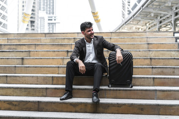 Business man sitting on stair with luggage in the routine of working with determination and confidence. concept of business trip travel and transportation.