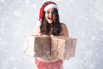 Christmas New Year concept of selling gifts. Model XXL in lingerie with presents. Fat woman in underwear. Happy plus size girl buy gift with discount. Big Female in santa claus hat with snowflakes