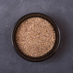 Cumin seeds in a bowl on a grey concrete background