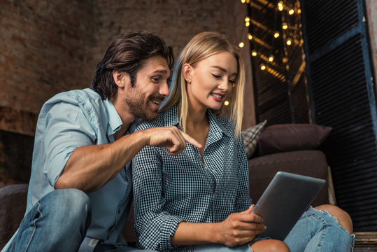 Couple at home watching tablet