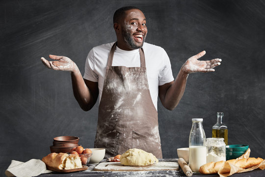 Uncertain male chef shrugs shoulders, has happy expression, doesn`t know what to bake, prepares dough, stands near kitchen table, isolated over black chalk background. Hesitant dark skinned baker