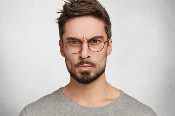 Headshot of strict annoyed aggressive man with beard, mustache, looks seriously through round spectacles, frowns face in dissatisfaction, expresses negative emotions, isolated over white concrete wall