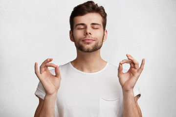Portrait of young adult male with beard, stands in yoga pose, tries to concentrate and feel relaxation after work, isolated over white background. People, meditation and mental practice concept