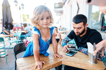 Dad and little daughter are sitting in a cafe