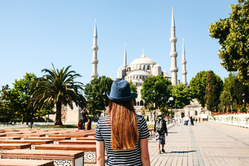 A young girl traveler in a hat from the back in Sultanahmet Square next to the famous mosque called the Blue Mosque in Istanbul, Turkey.