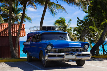 Aluminium Prints Old cars Amerikanischer blauer Mercury Oldtimer parkt am Strand unter Palmen in Varadero Cuba - Serie Cuba Reportage