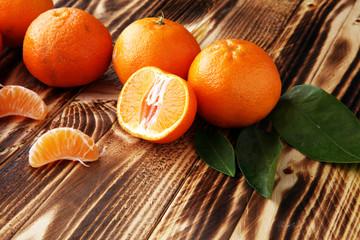 fresh mandarin oranges fruit with leaves on wooden table.