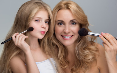 Favorite pastime. Portrait of happy mother and her playful little daughter are standing with naked shoulders and looking at camera with smile. They are applying make-up on face using brushes. Isolated