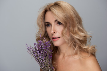 Elegant middle-aged blond woman with naked shoulders is standing with lavender. She is looking aside pensively. Isolated background and copy space